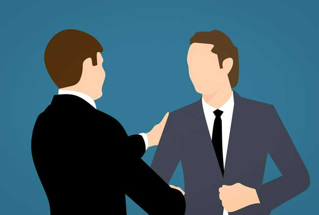 Image of two business men shaking hands in front a blue background