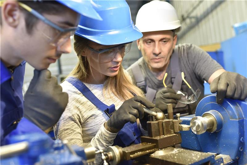 Three manufacturing employees training to operate a machine.
